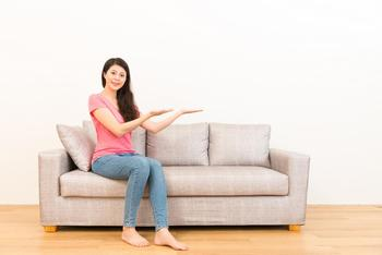 woman sitting on sofa with tailored loose covers